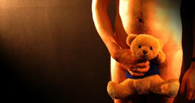 naked man holding teddy bear in front of genitals
