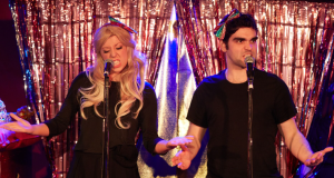 man and woman in front of glitter curtain singing