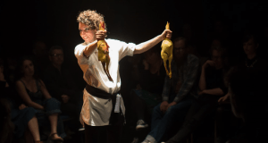 rachel mars in our carnal hearts a woman holding two skinned birds surrounded by an audience