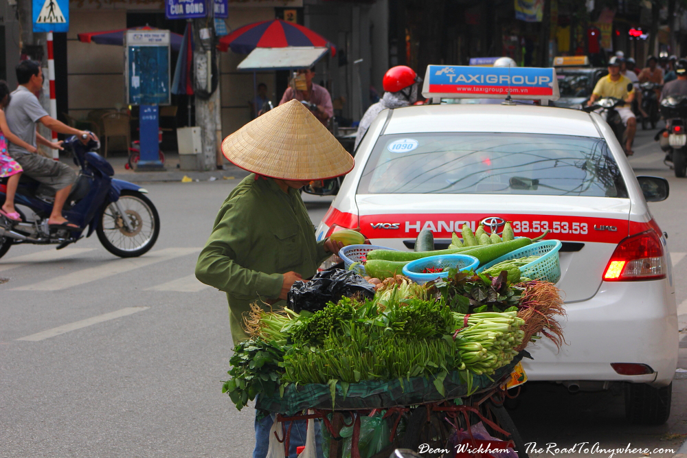 Man selling vegetables from a bicycle in Hanoi, Vietnam