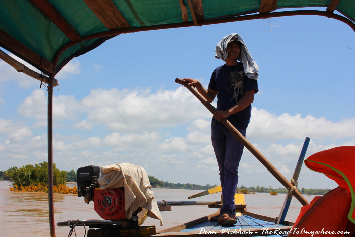 Boat driver paddling with an oar on the mekong river