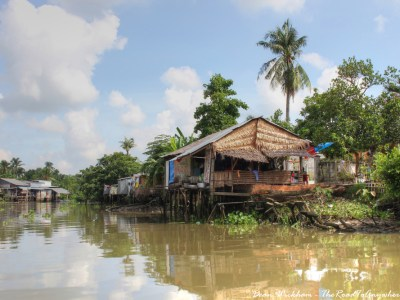 Meagre houses on the river in the Mekong Delta, Vietnam