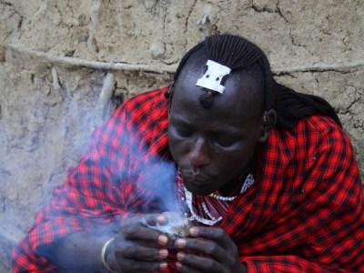 Masai man making fire with donkey dung in Lake Manyara, Tanzania