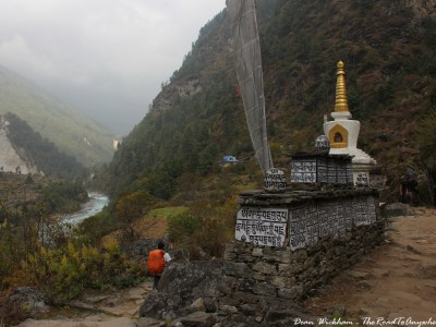 Walking past a mani wall and chorten on the trek from Surkhe to Phakding in Nepal