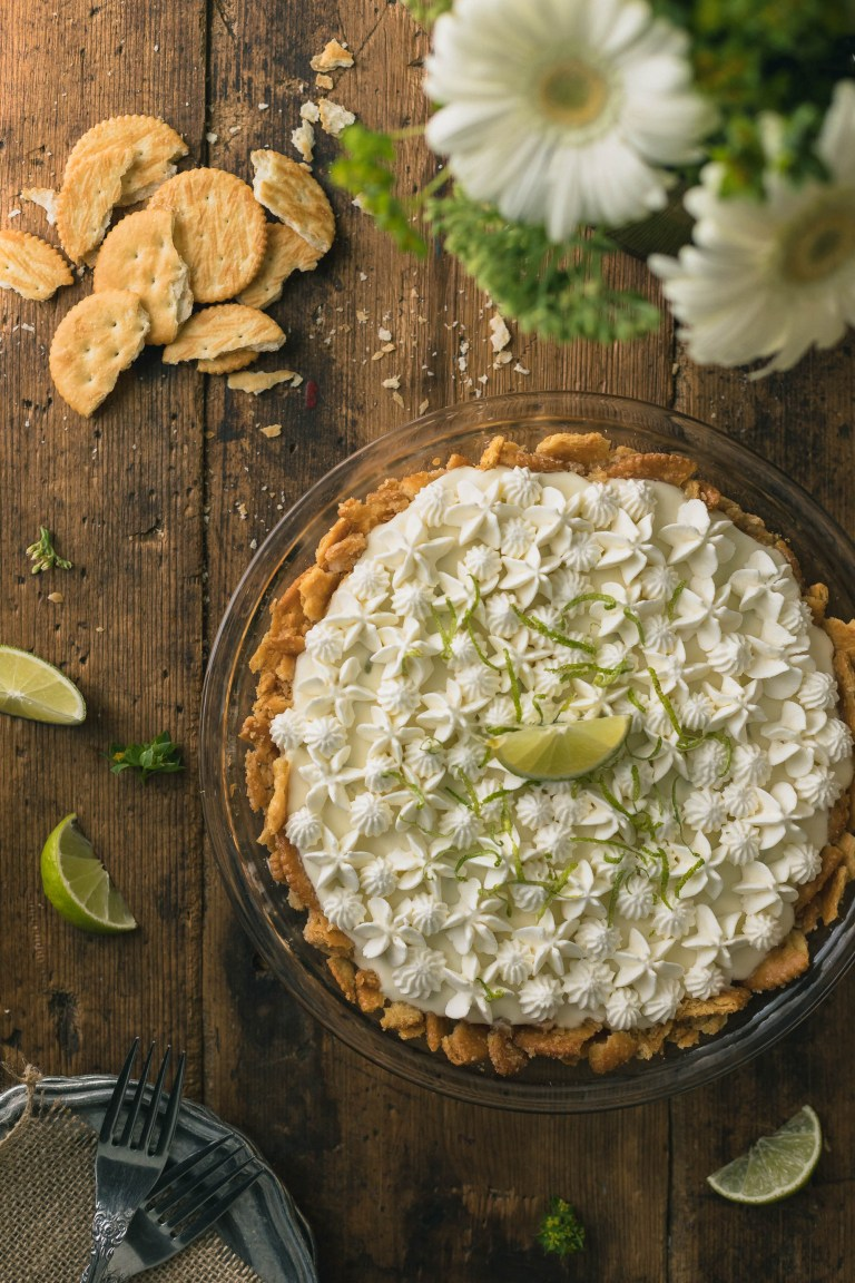 (Almost) No Bake Margarita Pie with Ritz Cracker Crust Recipe - A light & creamy lime Margarita filling is nestled into a buttery Ritz cracker crust, then frozen. This (almost) No Bake Margarita Pie with Ritz Cracker Crust is truly an easy treat that will help you keep your cool even when the temperatures are at full on sizzle.  And since it is virtually no bake (sans a quick toasting of the crust in the oven) you can rest assured your kitchen will keep its cool too.