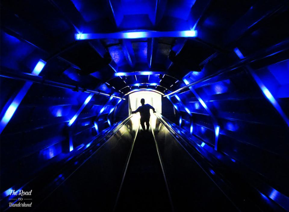 Going down the escalator in the disco-light tube