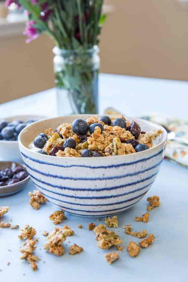Maple-sweetened Grain-Free Paleo Granola made with nuts and seeds. This refined sugar-free recipe yields huge granola clusters and is super crunchy and delicious for breakfast