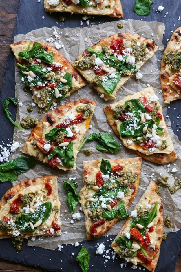 Hummus Flatbread with Sun-Dried Tomatoes, Spinach, and Pesto is an easy appetizer perfect for a healthy snack