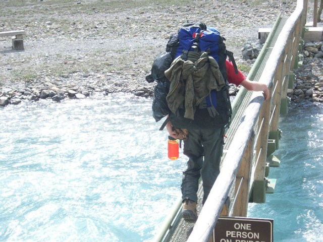 A student crosses one of the many bridges on the way to Berg Lake.