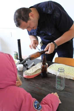 An RCMP officer showing how to remove prints from a bottle at an RCMP open house in 2014.