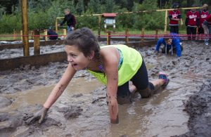 Photo: Evan Matthews Students from McBride & Valemount got down and dirty at the Otway Nordic Ski Club in Prince George last week. Kylie Ilnicki worms her way through the first obstacle with a smile on her face, but she says her favourite portion was swimming at the end. More photos below.