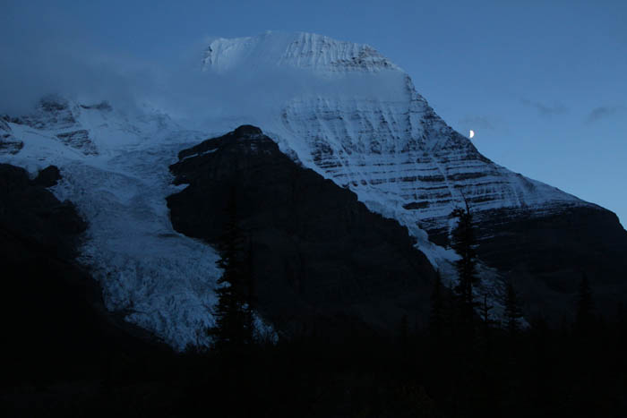 Photo: Dennis Pickerl The peak of Mount Robson makes it's way through the clouds, as the moon creeps around the mountain's side.