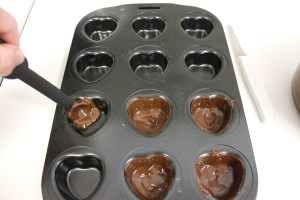 Coating the hearts with melted chocolate.