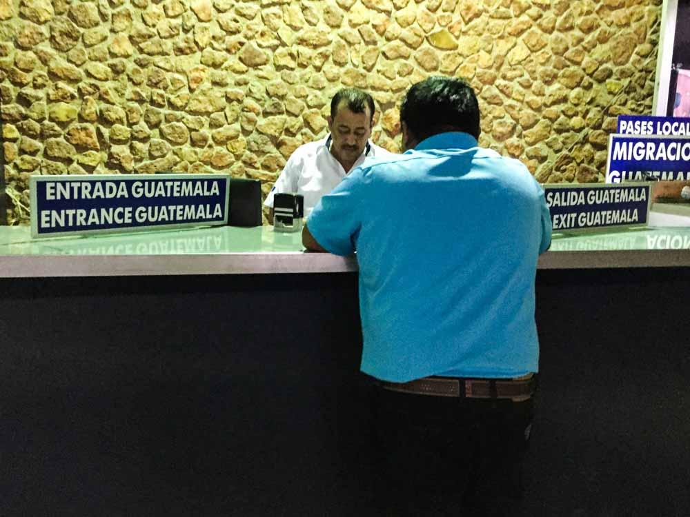 Man stamping passport at Guatemalan immigration land border