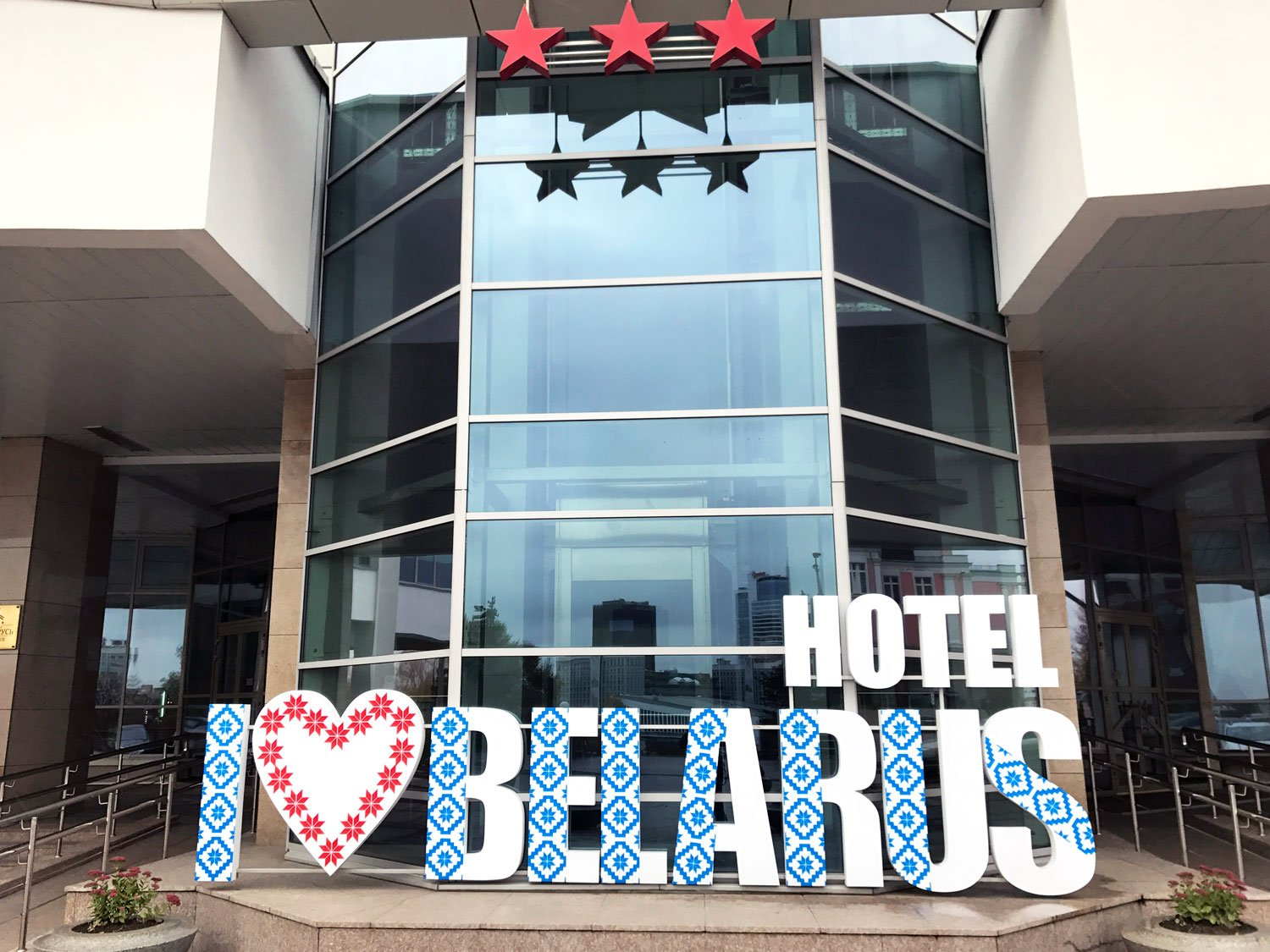 """Hotel Belarus with an I """"heart"""" Hotel Belarus sign in front and three red stars, indicating the class of the hotel"""
