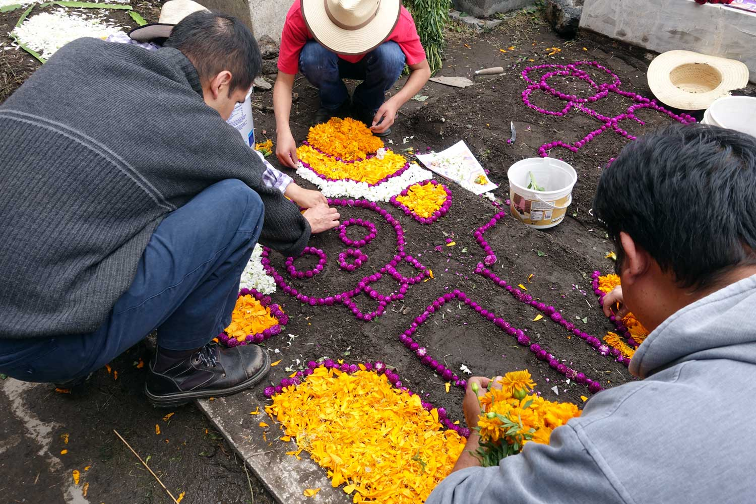 Relatives carefully begin the process of decorating the grave of an ancestor