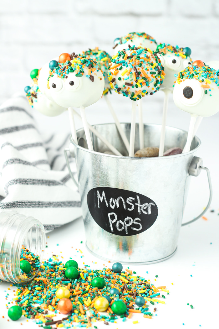 White chocolate dipped cake pops with sprinkles arranged in a tin pail.