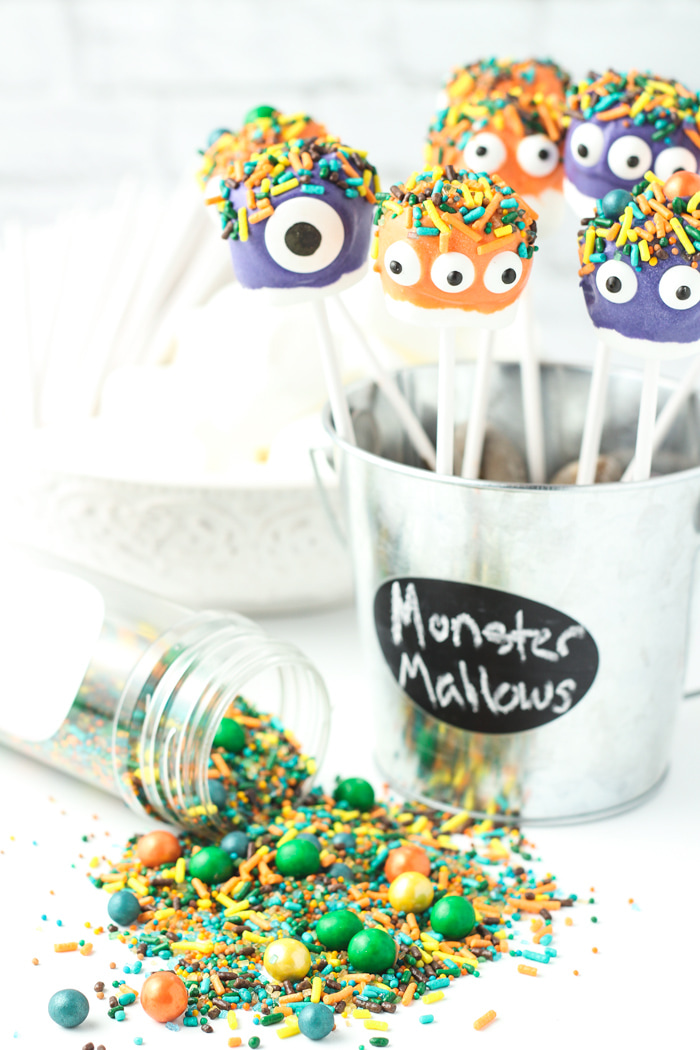 Marshmallows dipped in purple and orange dyed white chocolate with sprinkles and candy eyes.