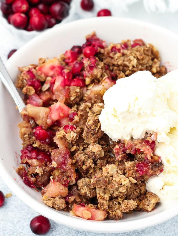 Gluten-free, vegan and refined sugar-free Cranberry Apple Pear Crisp in a bowl with ice cream.