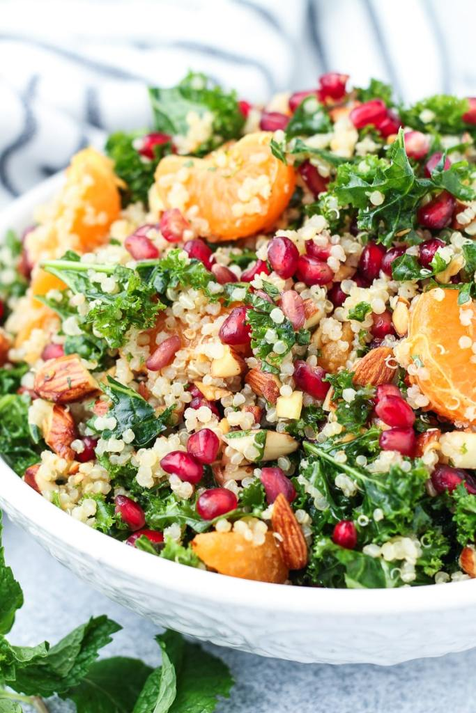 kale quinoa salad in a bowl with pomegranates and tangerines