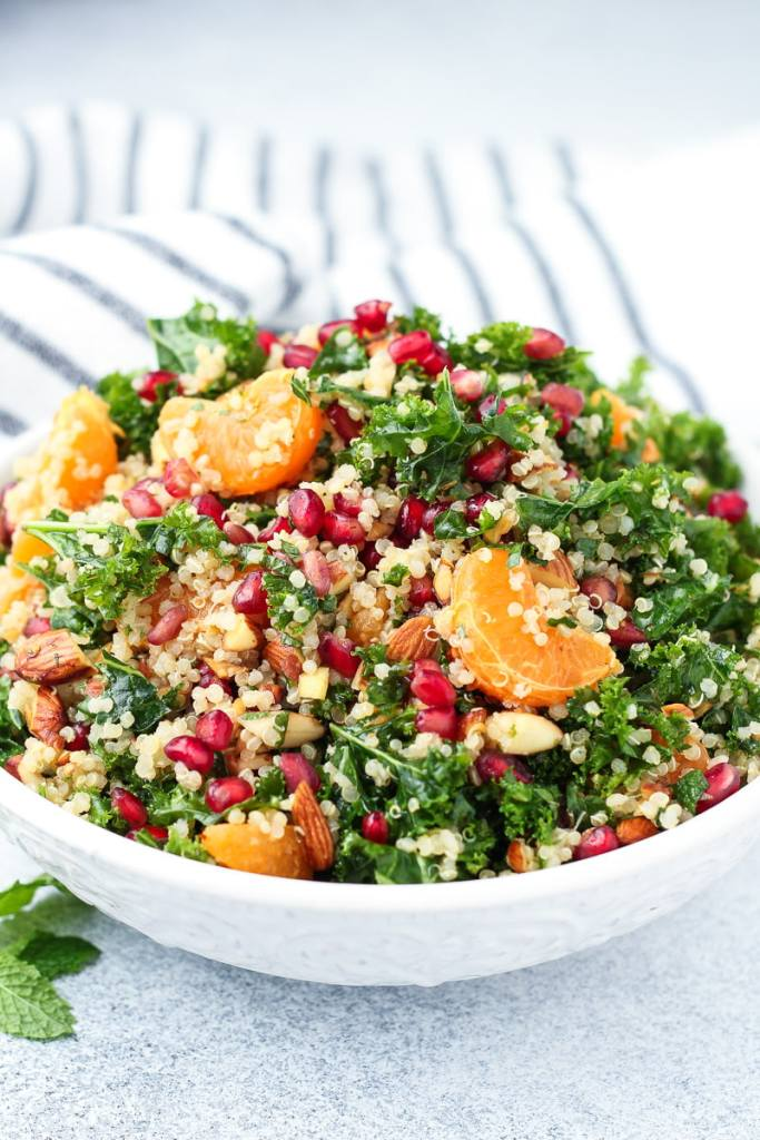 side view of quinoa pomegranate salad with kale and citrus vinaigrette.