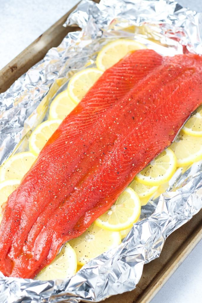 raw salmon on a tin foil lined cookie sheet with lemons tucked around the salmon.