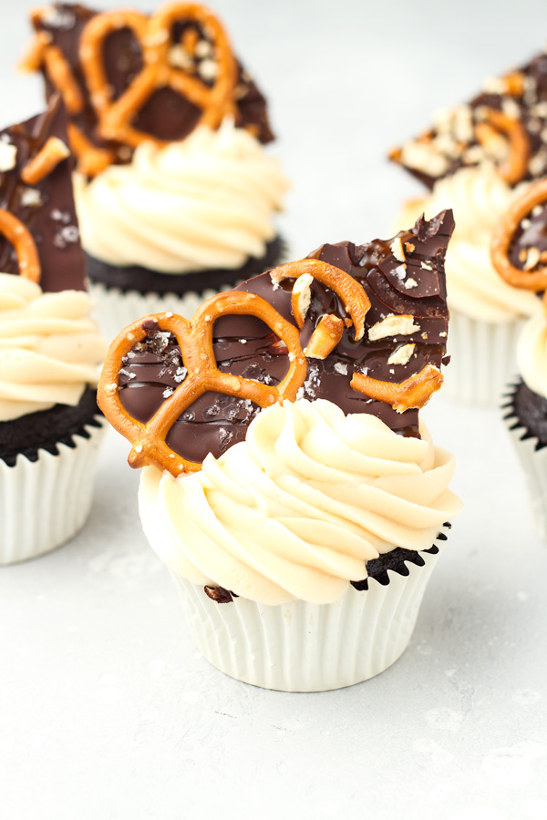 Close up shot of chocolate cupcakes with caramel buttercream, topped with pretzel bark.