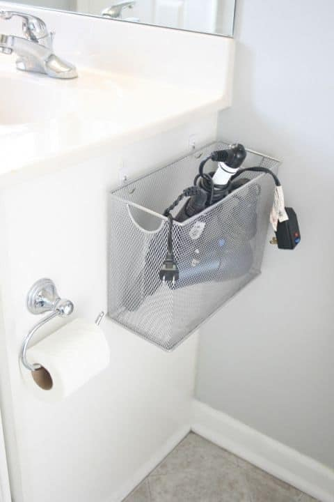 Bathroom Appliance Organizer Gone are the days of leaving the curling iron and hair dryer on the counter only to have it fall on the floor because there isn't enough space. This easy bathroom storage hack is simply attached to the vanity or wall. You can fill it will all sorts of items. thesawguy.com