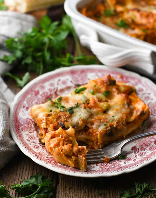 Side shot of a fork with a bite of easy vegetable lasagna on it.
