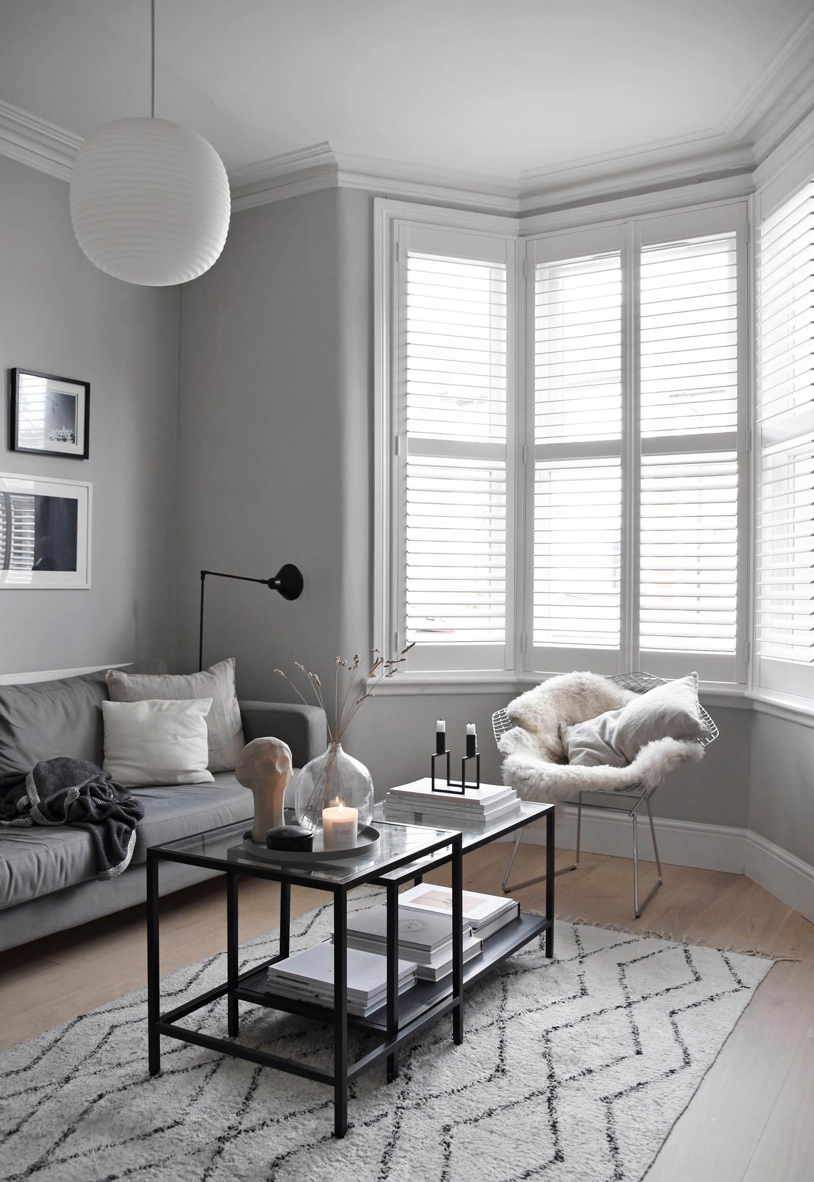 Minimalist grey living room with grey sofa, bay window shutters, white pendant lamp, black floor lamp and monochrome rug   How to design a lighting scheme that works for you   These Four Walls blog