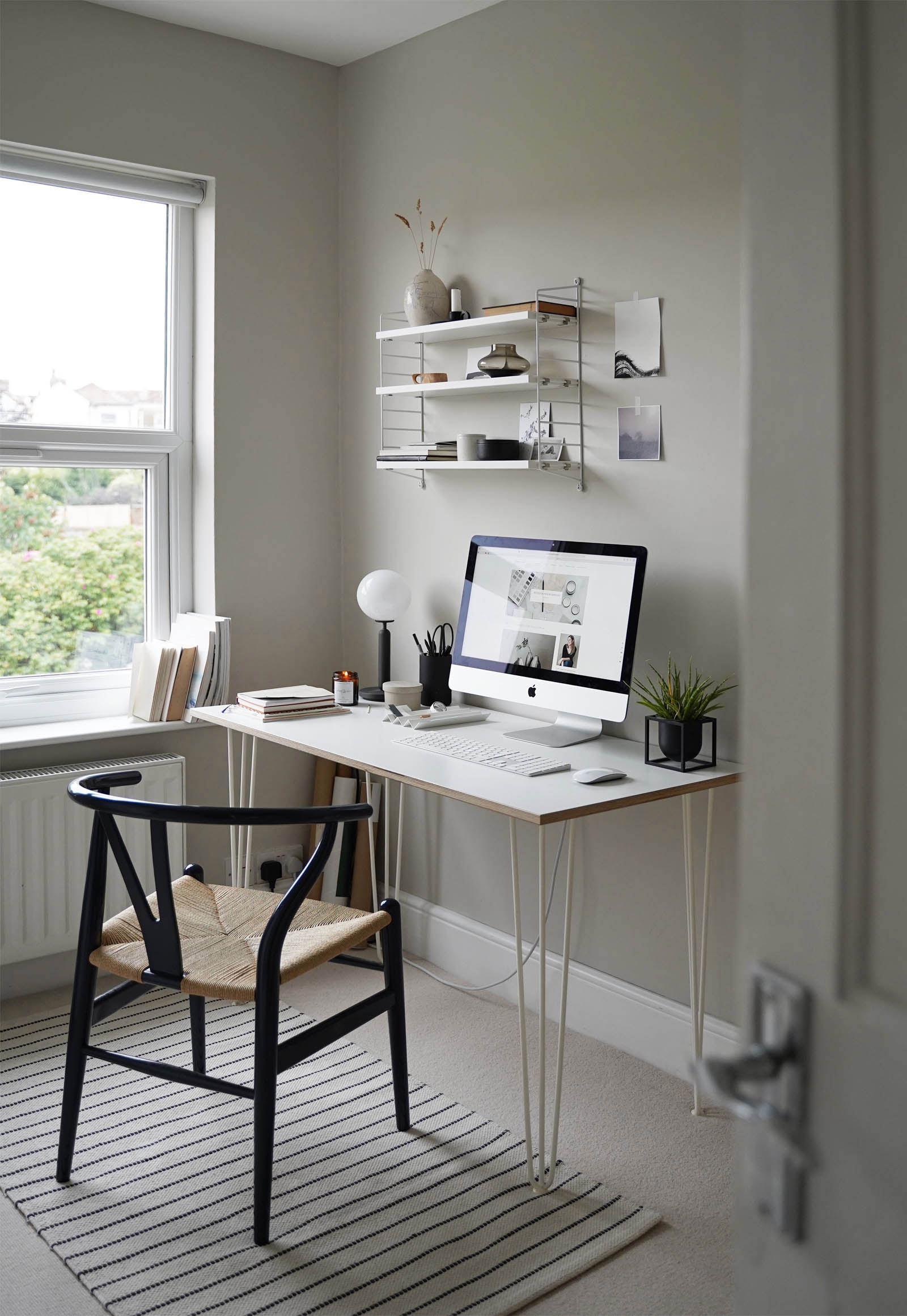 Calming grey home office with minimalist desk setup, String Pocket shelving, pale beige carpet and Wishbone chair | These Four Walls blog