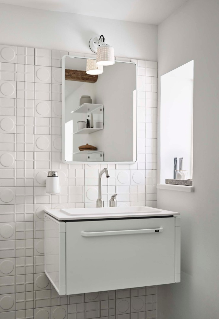 Minimalist white bathroom with embossed tiles and vanity unit at the Vipp Farmhouse - a designer holiday cottage in the Danish countryside   These Four Walls blog