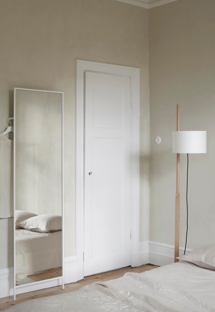 Simple beige bedroom with textured walls and a full-length white-framed mirror by Design Of | These Four Walls blog