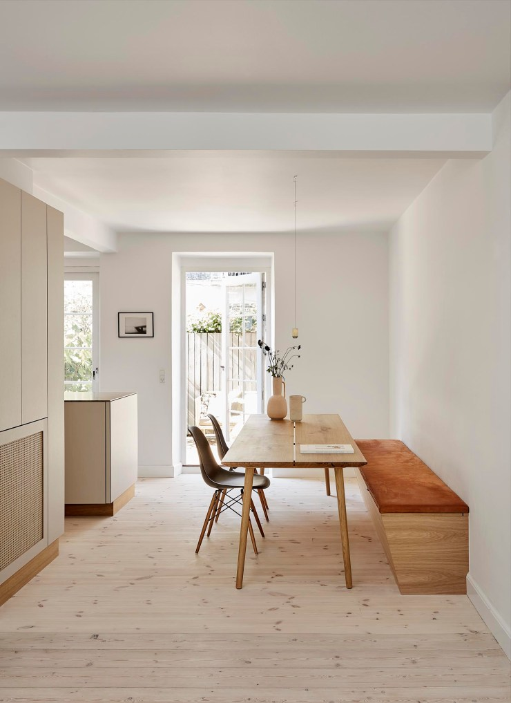 A warm, minimalist beige kitchen with an open-plan dining area and built-in bench seat   These Four Walls blog