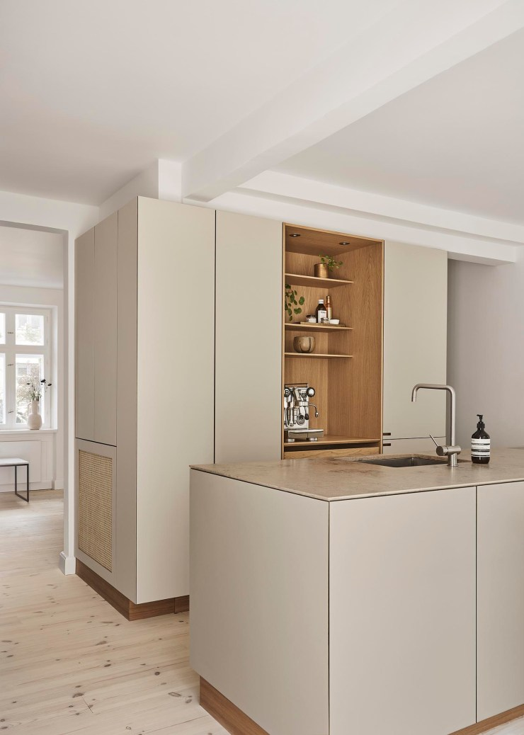 A warm, minimalist kitchen in beige and oak, with open niche, display shelves and island unit   These Four Walls blog
