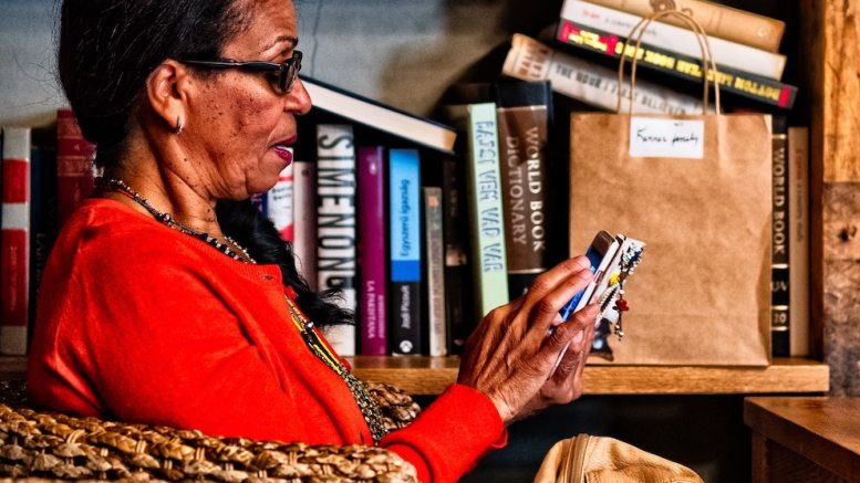 A Black woman sits in a wicker chair beside a bookcase, reading her phone.