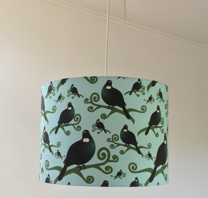 A pendant lampshade haning from the ceiling. The design features an illustration of many tui on a blue background.