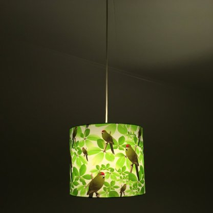 kakariki pendant light shade, with light shining through it.