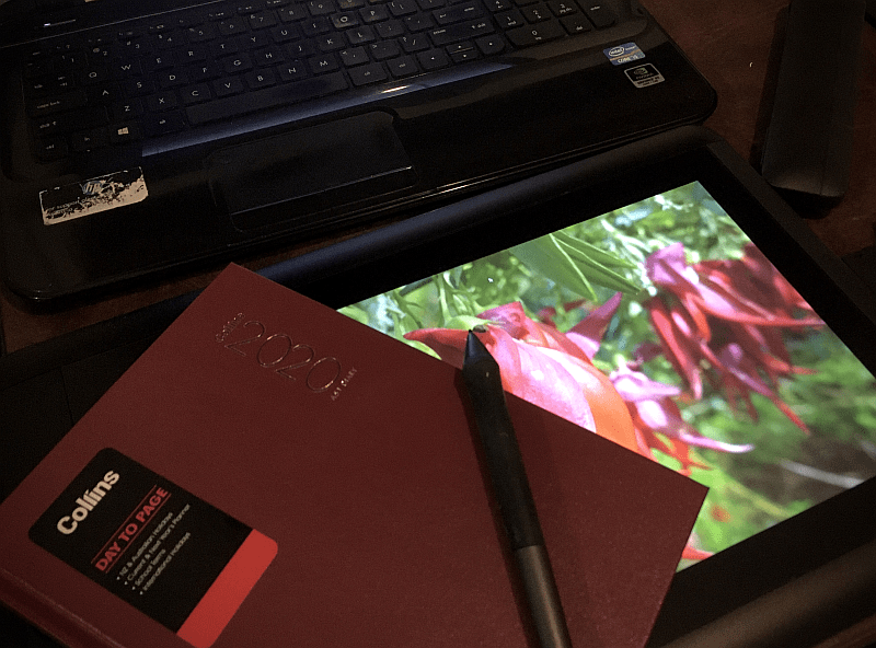 Photo of desktop showing a diary, drawing tablet, and the keyboard of a laptop.