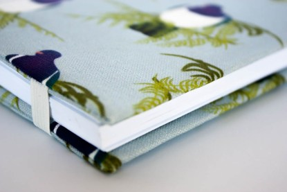 Product photograph showing detail of the edge of the cover with the elastic in place to hold it closed.