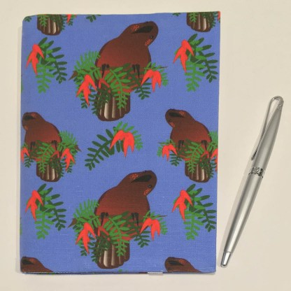Product photograph showing the front of the cover with a pen for context.