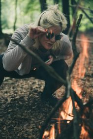 woman in sunglasses with phone crouching by campfire