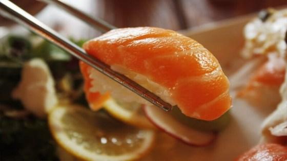 Sushi held be metal chopsticks