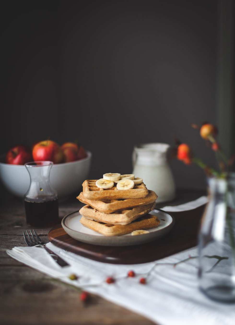 a stack of waffles with maple syrup sitting next to it and a bowl of apples in the background.