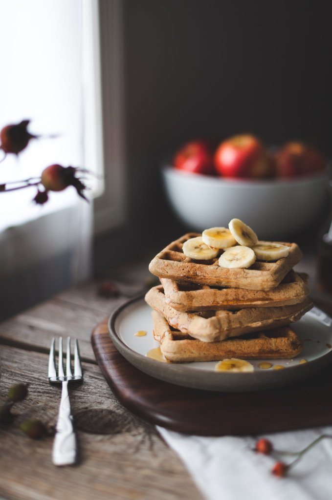 a stack of a waffles with banana slices on top sitting next to a window.