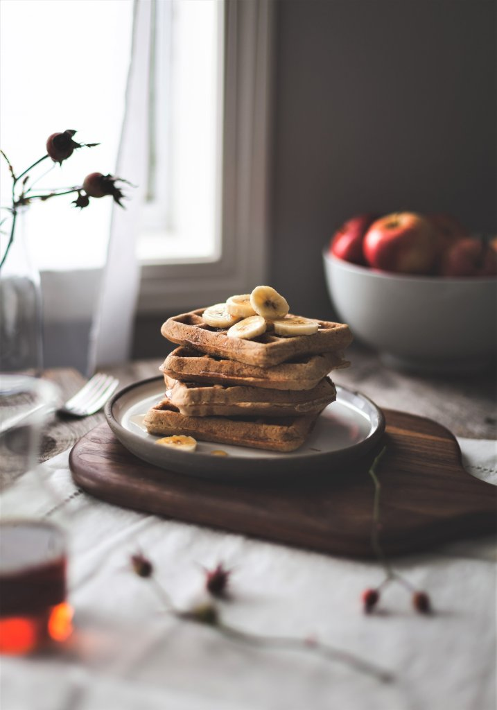 A stack of vegan-gluten-free waffles sitting on a plate next to a window.