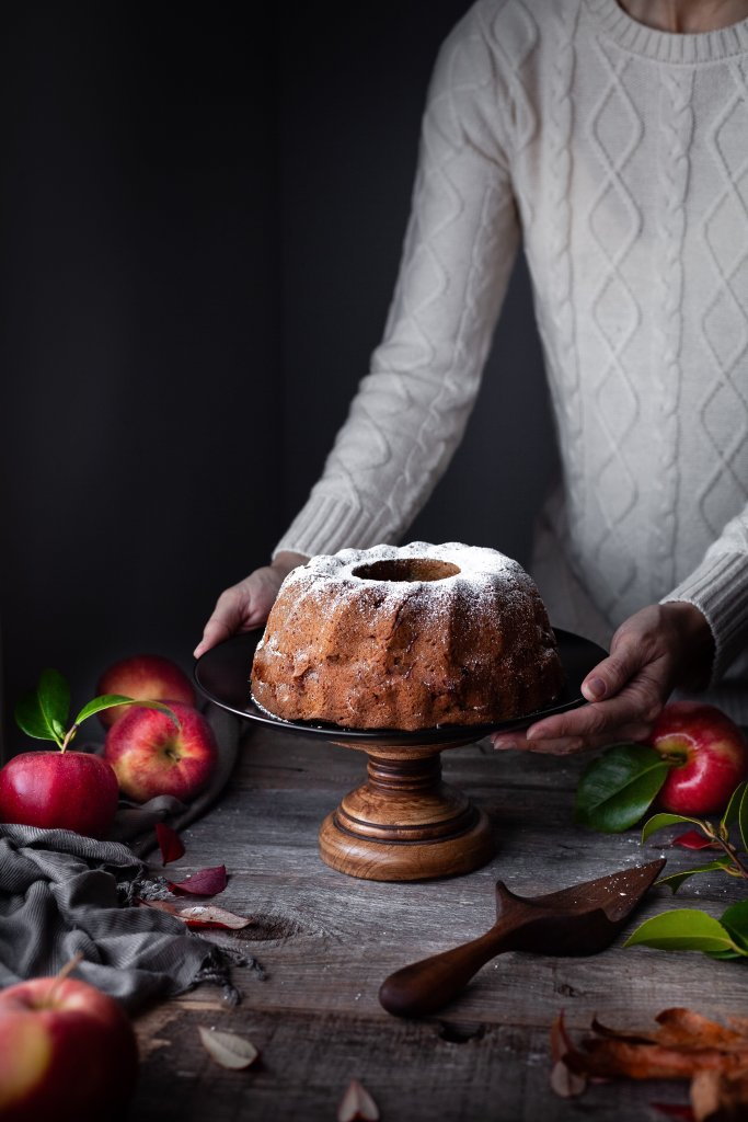 head on image of vegan apple spice cake with bakers hands.