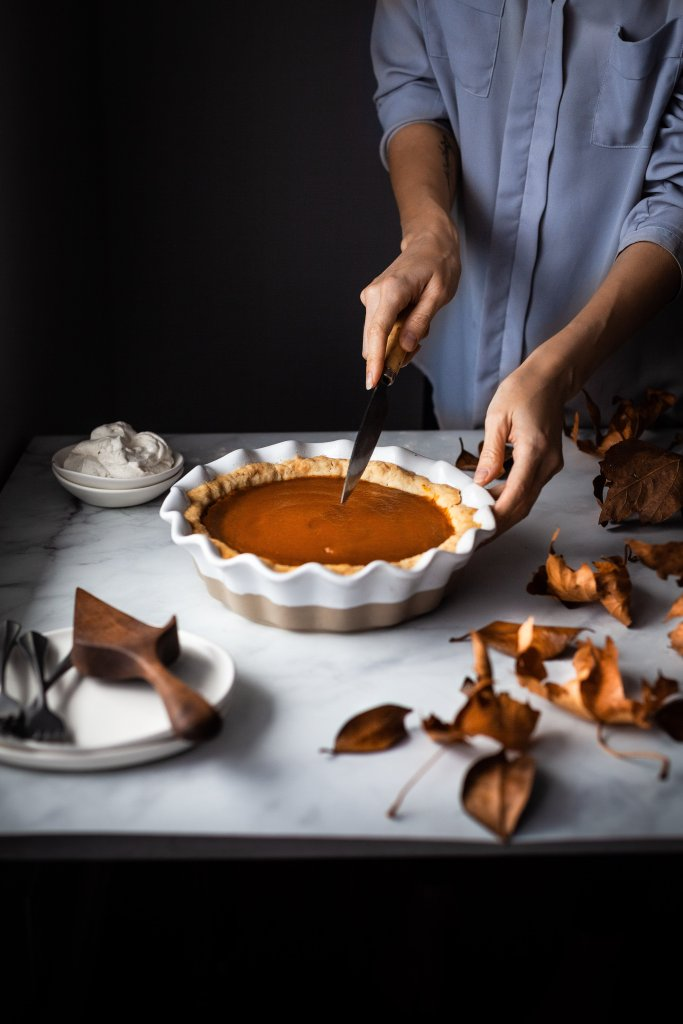 head on image of vegan pumpkin pie with a baker cutting out a slice.