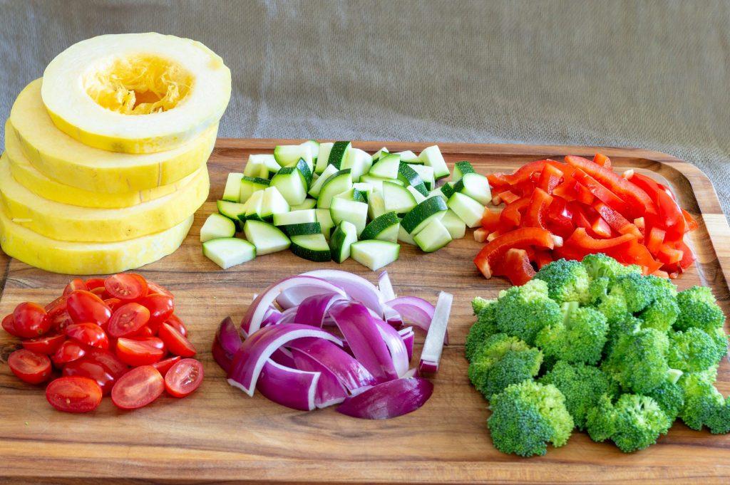 spaghetti squash, broccoli, peppers, onion, tomatoes chopped on a cutting board