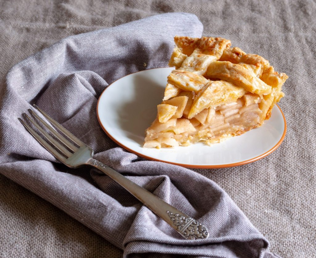 slice of cheddar apple pie sitting on white plate